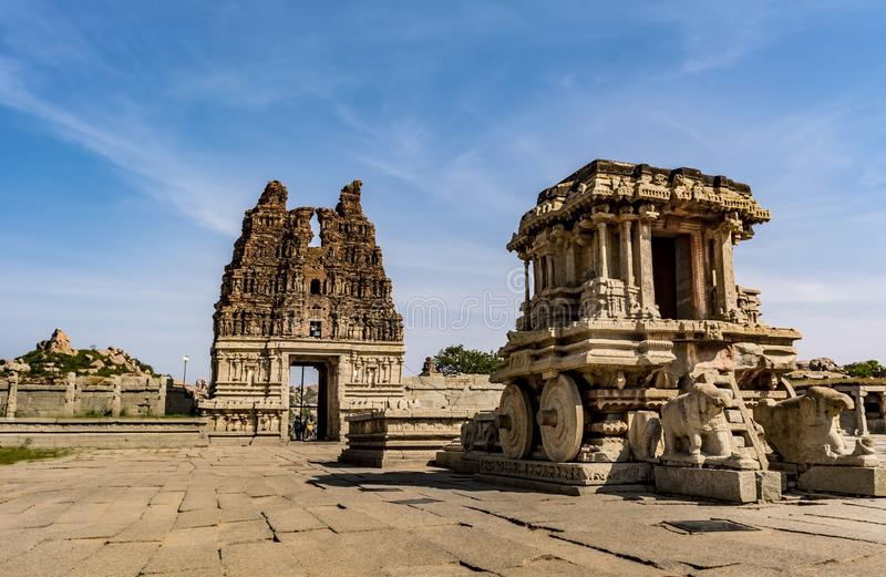 Stone Chariot and Ruined Tower - Vittala Temple Hampi. The chariot is actually a shrine dedicated to Garuda, built inside the Vittala Temple Complex. ... The stock image