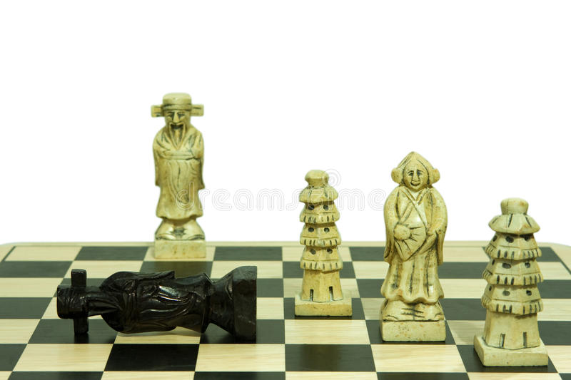 Stone chess set checkmate move isolated on white. A stone chess set showing a checkmate move on the black king isolated on white background royalty free stock photography