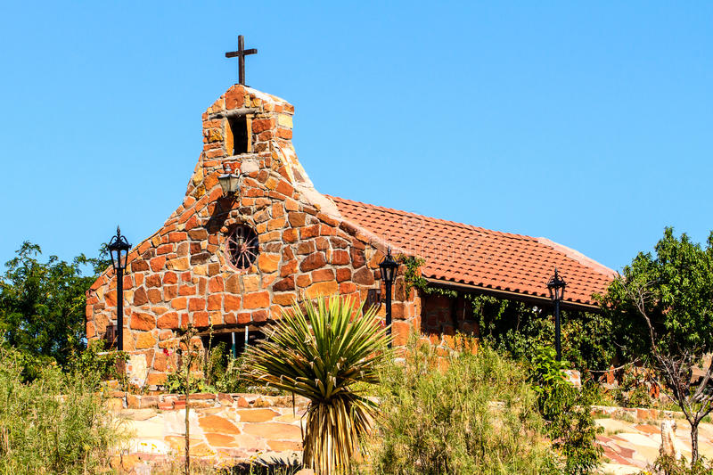 Stone Church in New Mexico. This image of a stone church was captured near Santa Fe, New Mexico. There is a nice wheel on the front of the building royalty free stock photo