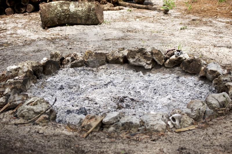 Stone circle fire pit with ash. A stone circle fire pit filled with ash from recent fire royalty free stock photography