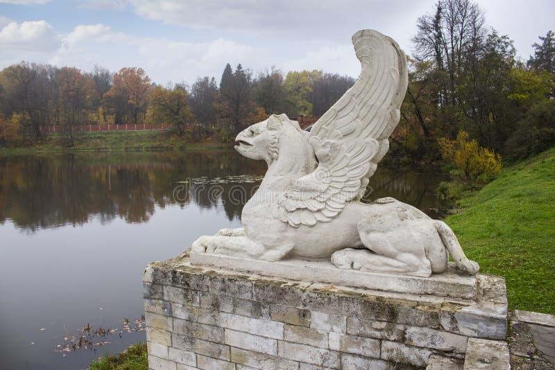 Stone concrete lion with wings statue, gargoyle on stone pedestal, shore of pond lake autumn landscape stock images