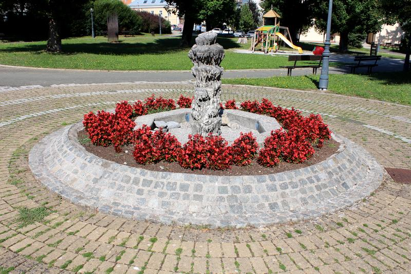 Stone and concrete sculpture inside public park surrounded with densely planted small red flowers and concrete tiles. On warm sunny summer day royalty free stock photos