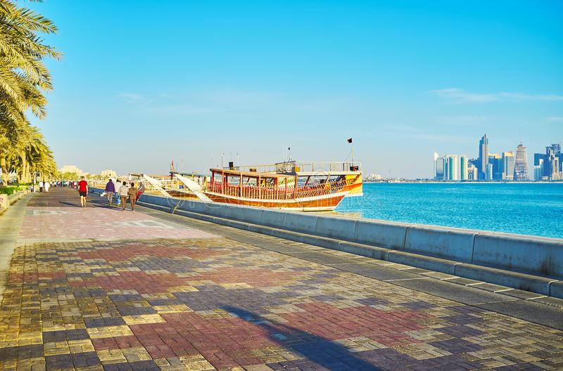 Walk along Doha embankment, Qatar. The stone Corniche promenade is one of the main city locations, stretching along coastal districts and popular among the stock photos