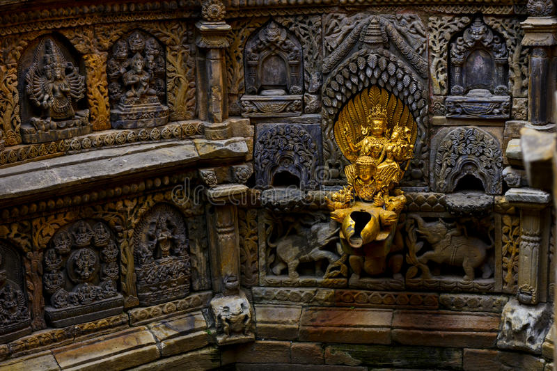 Stone crafted gods in Lalitpur Nepal. Sacred golden water fountain inside the palace in Lalitpur Nepal stock photos
