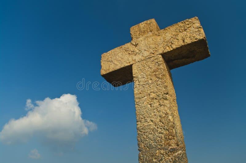 Stone cross against blue sky on sunny day stock photo