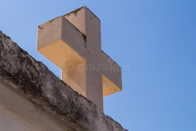 Stone cross and a blue sky. Wall and a heavy cross made of stone. Summer blue sky in the background. Primosten, Croatia royalty free stock image