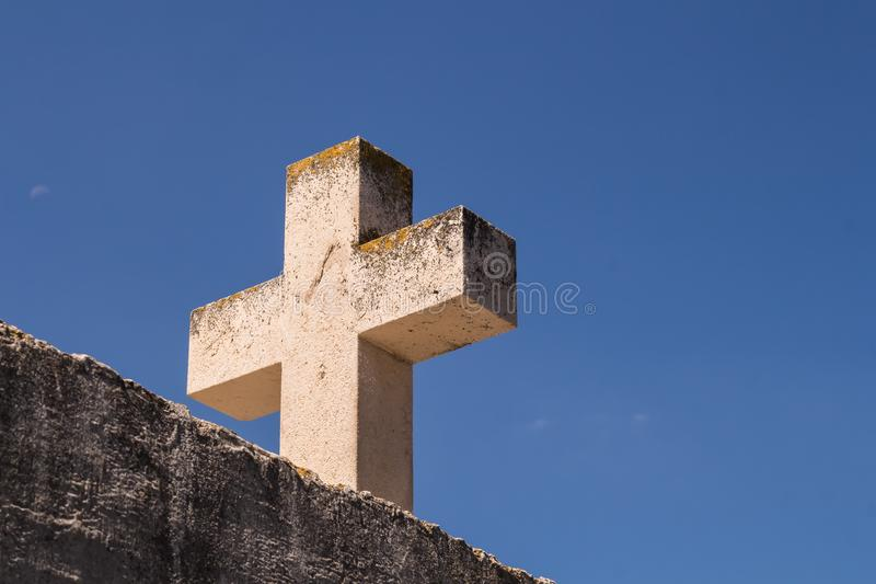 Stone cross and a blue sky. Wall and a heavy cross made of stone. Summer blue sky in the background. Primosten, Croatia stock image