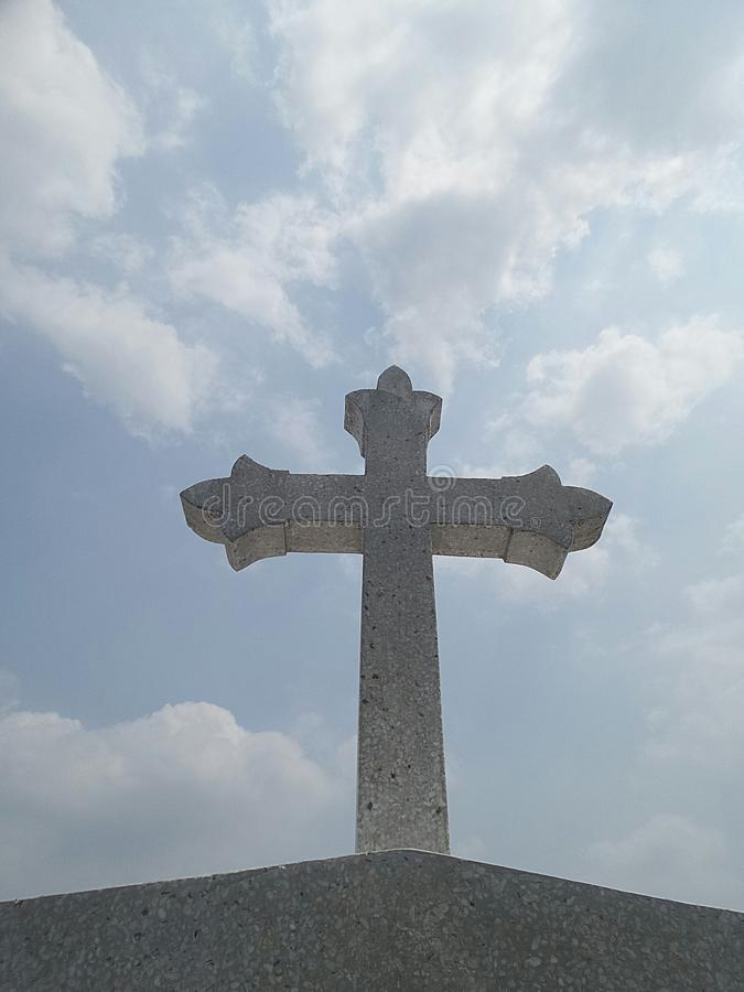 Stone cross and bright blue sky stock images