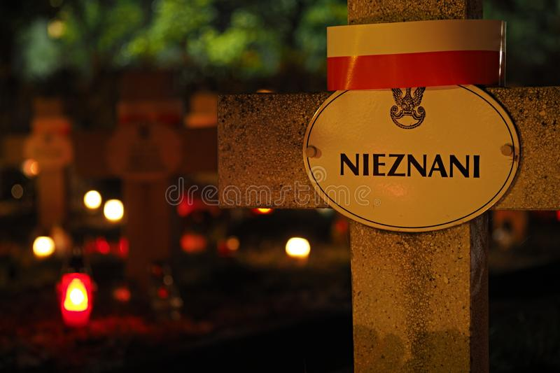 Stone cross on the grave of unknown soldiers at night royalty free stock image