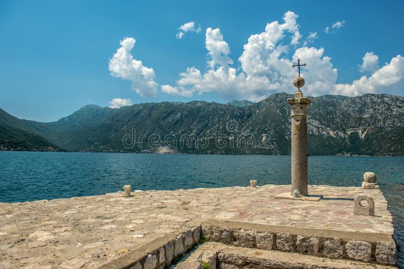 Stone cross on the island of St. Jerzego Ostrów, Sveti Dorde. One of two islets near the coast of Perast in the Bay of Kotor. royalty free stock photography