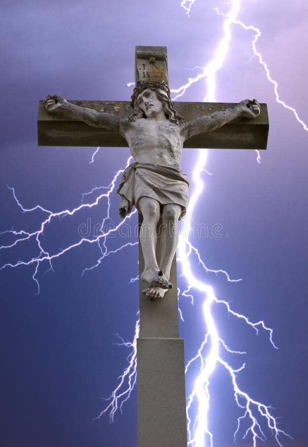 Stone cross with Jesus and sky with lightning royalty free stock photo