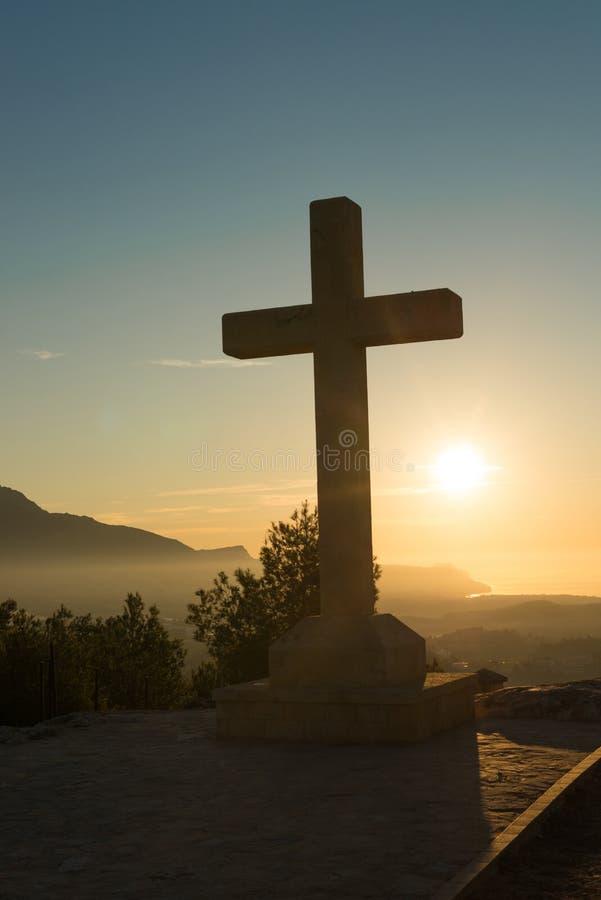 Stone cross under the sunrise. Christian stone cross under the warm light of sunrise stock images