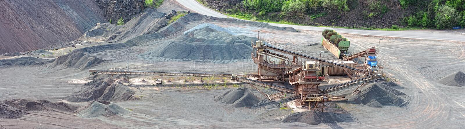 Stone crusher machine in an open pit mine. Panoramic images of a stone crusher machine in an open pit mine. mining industry. images created of 5 seperate images stock photo