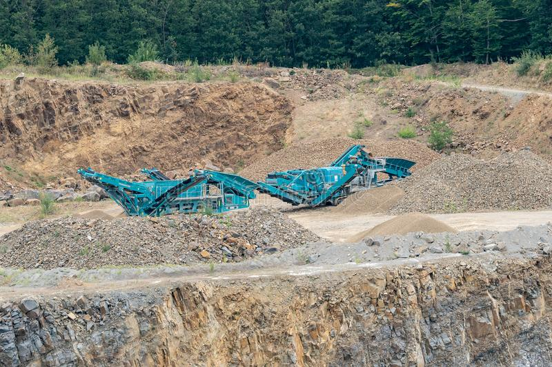Stone crusher in the quarry. Working mining machine - stone crusher. Quarrying of stones for construction works. Mining industry. stock photography