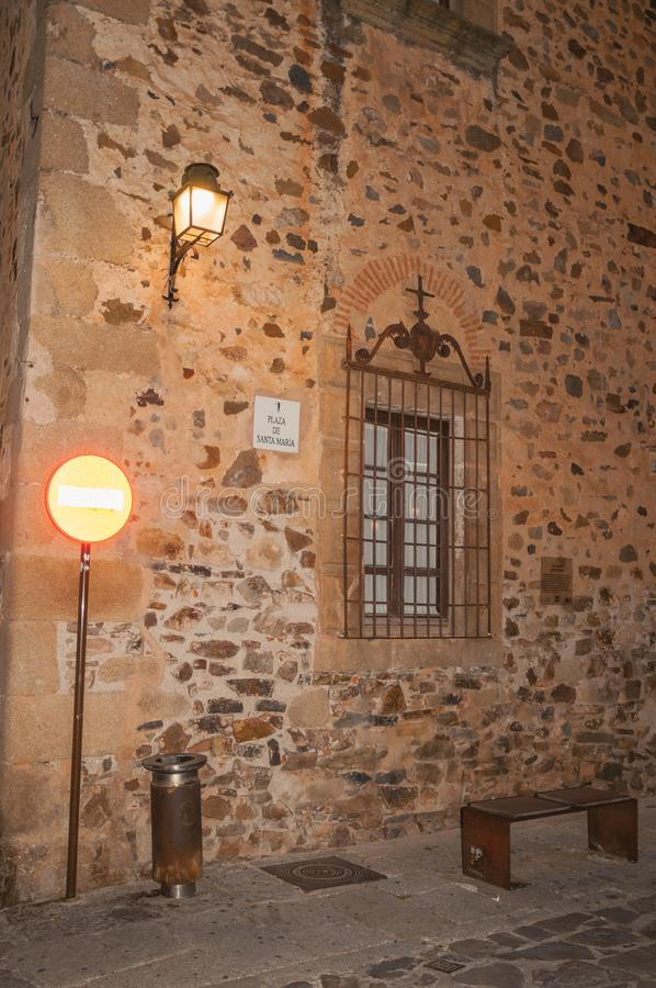 Stone facade with lamp, barred window, bench and transit sign at dusk in Caceres. A cute and charming town with a fully preserved medieval city center in stock image