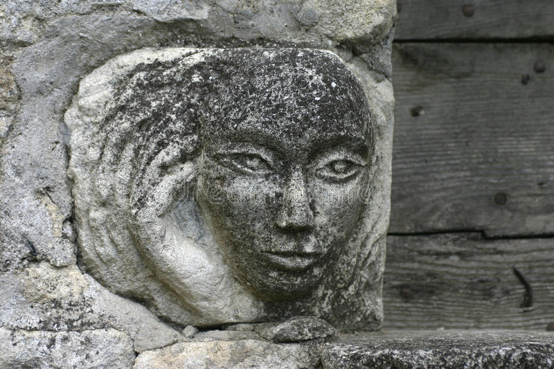 A stone face carving in Oppède le Vieux in the Luberon. A detail study. Oppède-le-Vieux, its narrow, broken, cobbled streets leading up to its 12th royalty free stock images