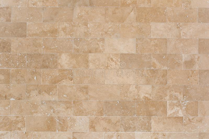 Stone facing of beige wall made of travertine. Texture of masonry. stock photography