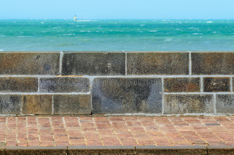 stone fence stone fence wall and pavement next to the sea stock photo image
