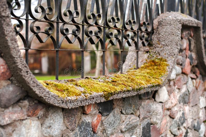 Stone fence with wrought-iron fence and moss. Close up - stone fence with wrought-iron fence and moss royalty free stock photos