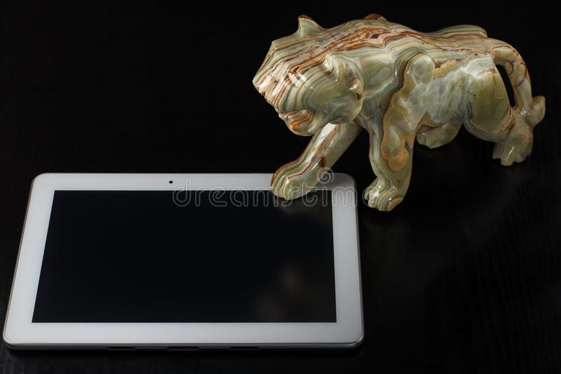 Stone figure of a tiger and the tablet. Onyx stone figure of a tiger and the tablet computer on a black background royalty free stock photos