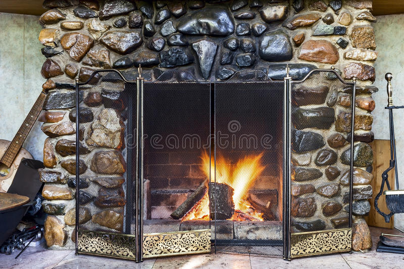 Stone fireplace. In country house and fire blazing inside with natural light royalty free stock photo