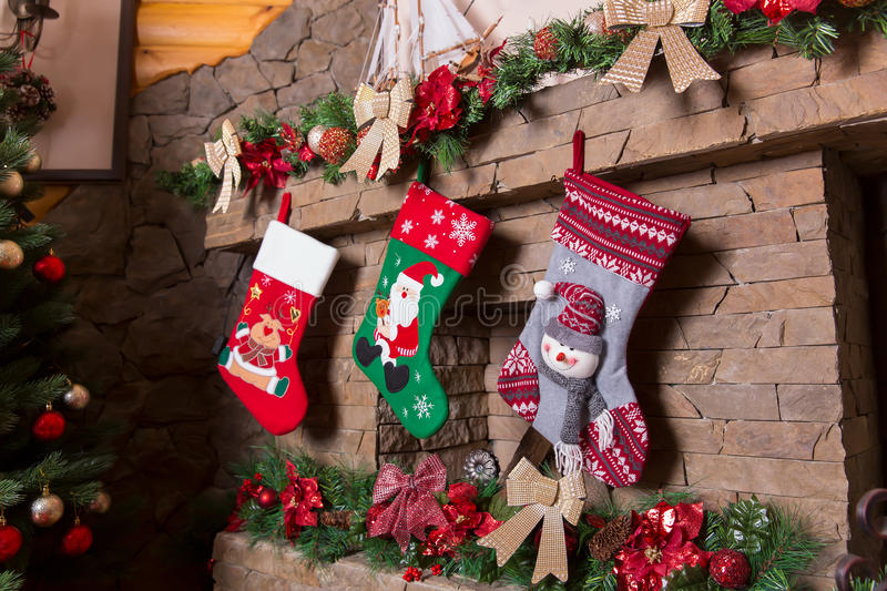 Stone fireplace decorated with christmas stockings. Xmas tree and holiday decoration on background royalty free stock photo