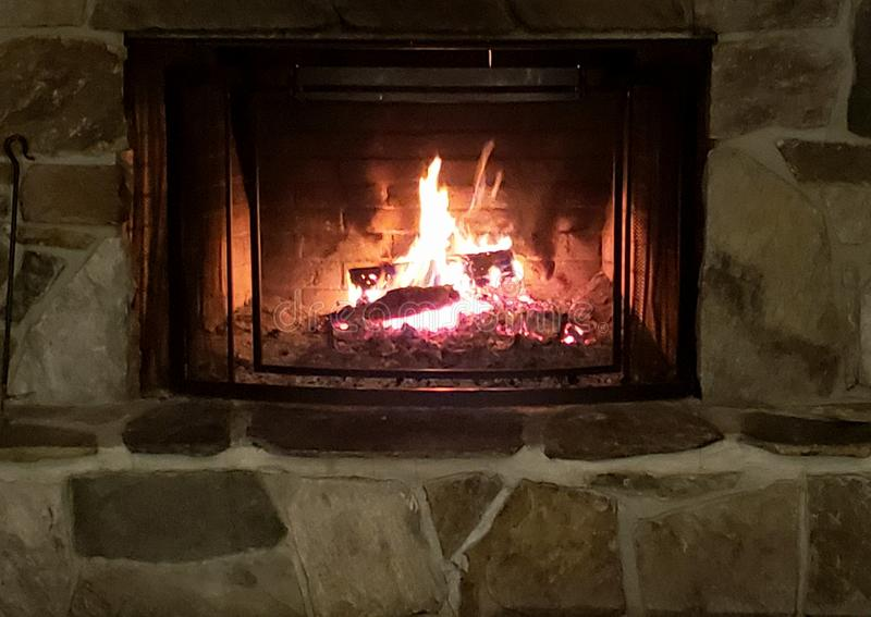 Stone Fireplace Glowing Hot. Ambiance winter comfort hotcoals relaxation skilodge stonework warmth cozy royalty free stock photo