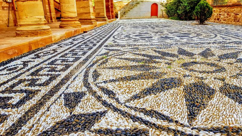 Stone mosaic in front of Church in Thimiana Chios Greece. Stone floor mosaic in front of Church in Thimiana Chios Greece  Design using natural stones from the royalty free stock image