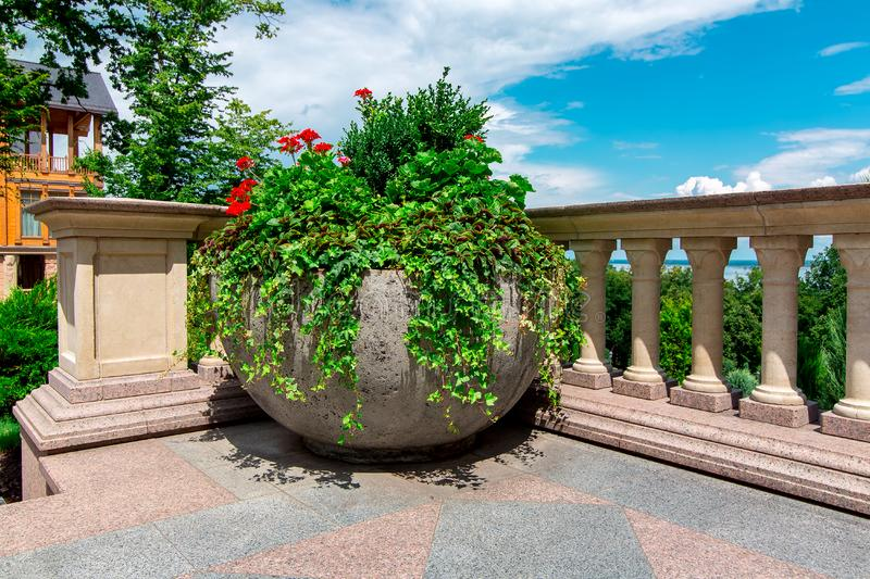 Stone flowerpot with flowers on the balcony with railings and balustrades. Stone flowerpot with flowers on the balcony with railings and balustrades in the royalty free stock photography