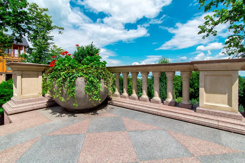Stone flowerpot with flowers on the terrace with railings and balustrades. Stone flowerpot with flowers on the terrace with railings and balustrades in the royalty free stock images