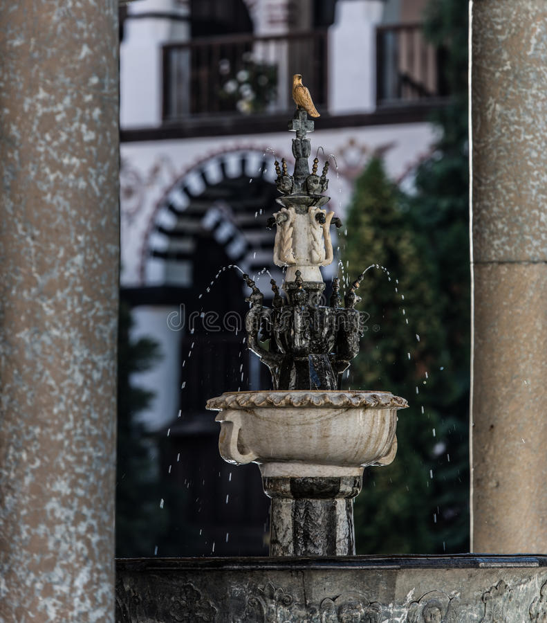 Stone Fountain. A small stone fountain with marble decorations and a small swallow sculpture sitting on top, found in the courtyard of the Rila Monastery of royalty free stock photography