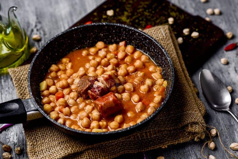 Garbanzos a la riojana, a spanish chickpeas stew. A stone frypan with garbanzos a la riojana, a spanish chickpeas stew, on a wooden chopping board placed on a royalty free stock photo