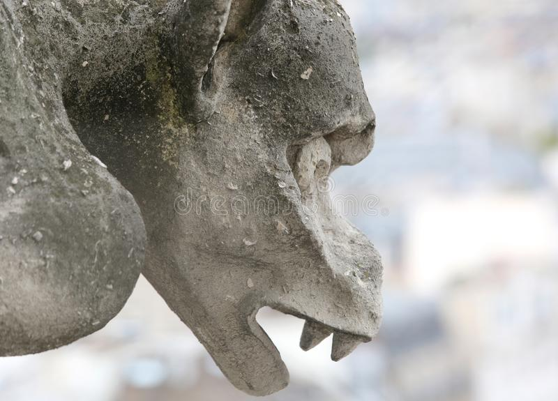 Stone gargoyle on the facade of the church of Notre Dame. In Paris stock image