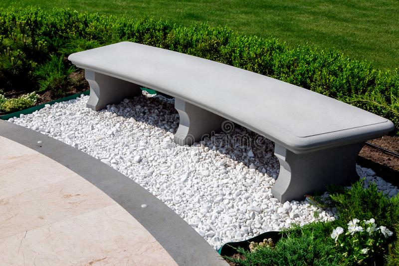 Stone gray bench strewn with white stone pebbles in a garden. royalty free stock photo