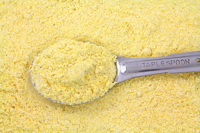Stone ground yellow corn meal with tablespoon. A filled tablespoon atop a layer of stone ground yellow corn meal stock image
