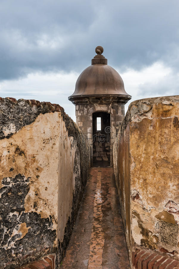Stone gun turret on Castillo San Felipe del Morro. With stormy sky and rain soaked walls royalty free stock images