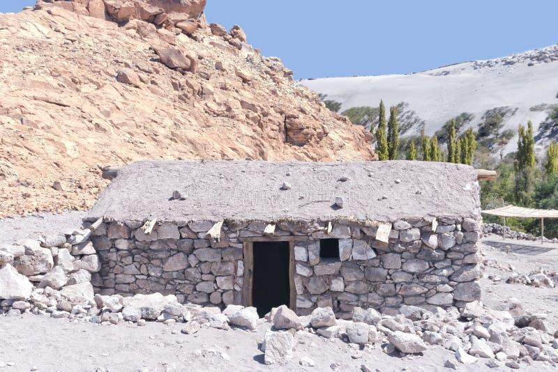 Stone house in desert oasis next to sand dunes stock photos