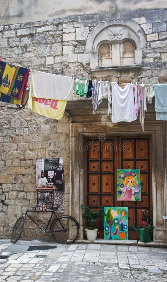Stone house in narrow street of old town, beautiful architecture with old door, laundry and bicycle, Trogir, Dalmatia, Croatia stock photo