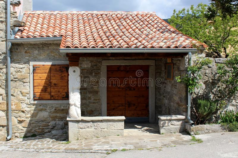 Stone house with new roof tiles. Traditional Mediterranean stone house with new roof tiles, wooden windows blinds and drain pipe royalty free stock photography