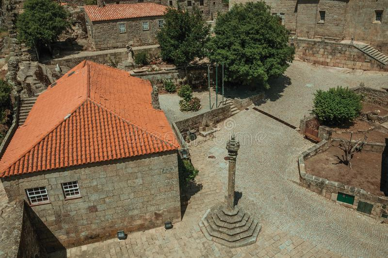 Stone houses and chapel encircling a square with pillory. Stone gothic houses and chapel encircling a deserted square on slope with pillory, in a sunny day at stock photo