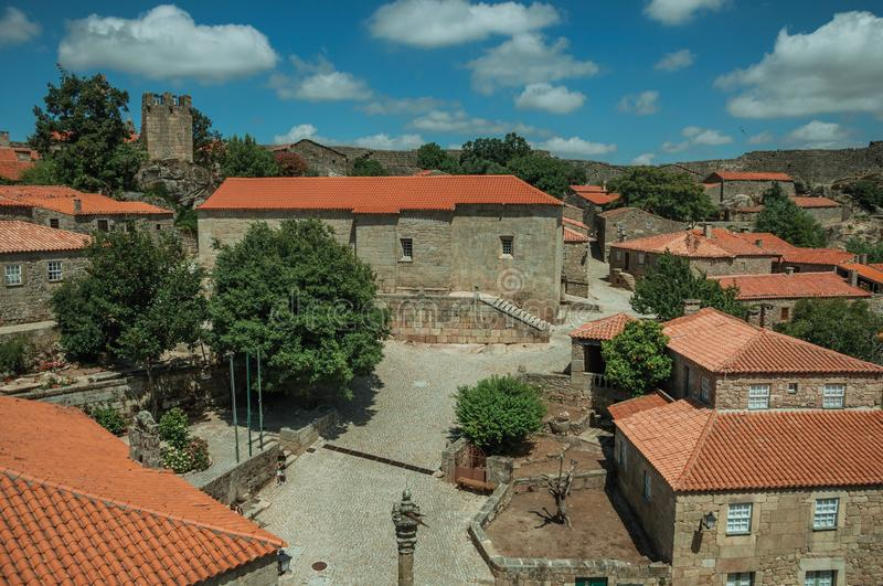 Stone houses and chapel encircling a square with pillory. Stone gothic houses and chapel encircling a deserted square on slope with pillory, in a sunny day at stock photography