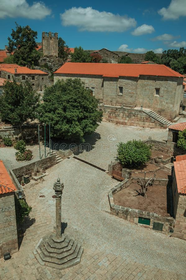 Stone houses and chapel encircling a square with pillory. Stone gothic houses and chapel encircling a deserted square on slope with pillory, in a sunny day at stock images
