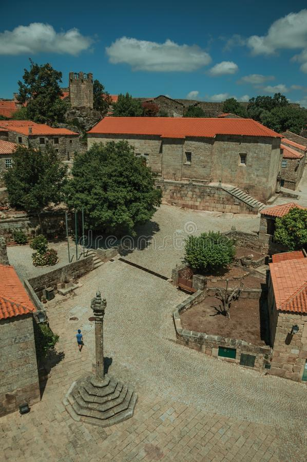 Stone houses and chapel encircling a square with pillory. Stone gothic houses and chapel encircling a deserted square on slope with pillory, in a sunny day at royalty free stock images