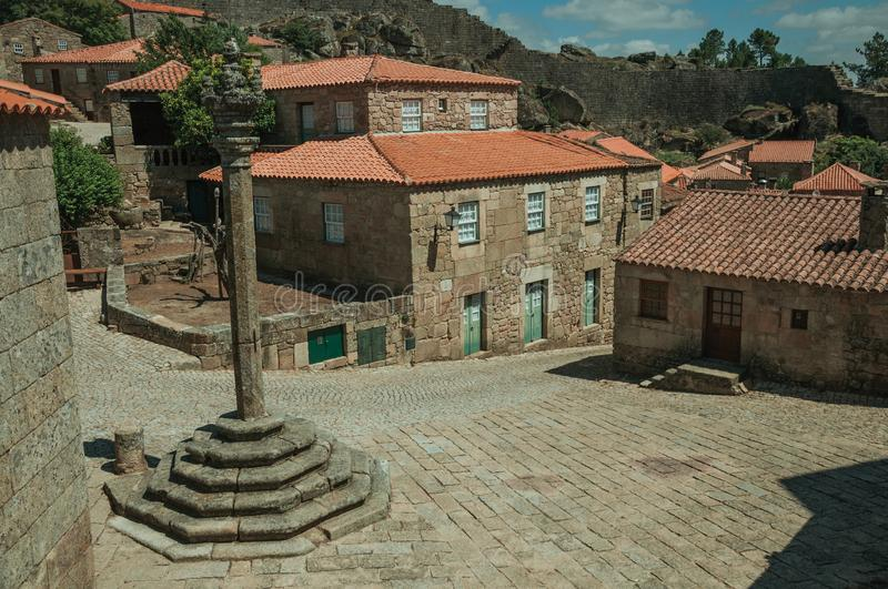 Stone houses and chapel encircling a square with pillory. Stone gothic houses and chapel encircling a deserted square on slope with pillory, in a sunny day at stock image