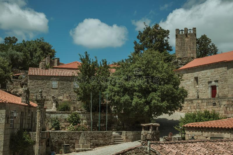 Stone houses and chapel encircling a square with pillory. Stone gothic houses and chapel encircling a deserted square on slope with pillory, in a sunny day at royalty free stock photography