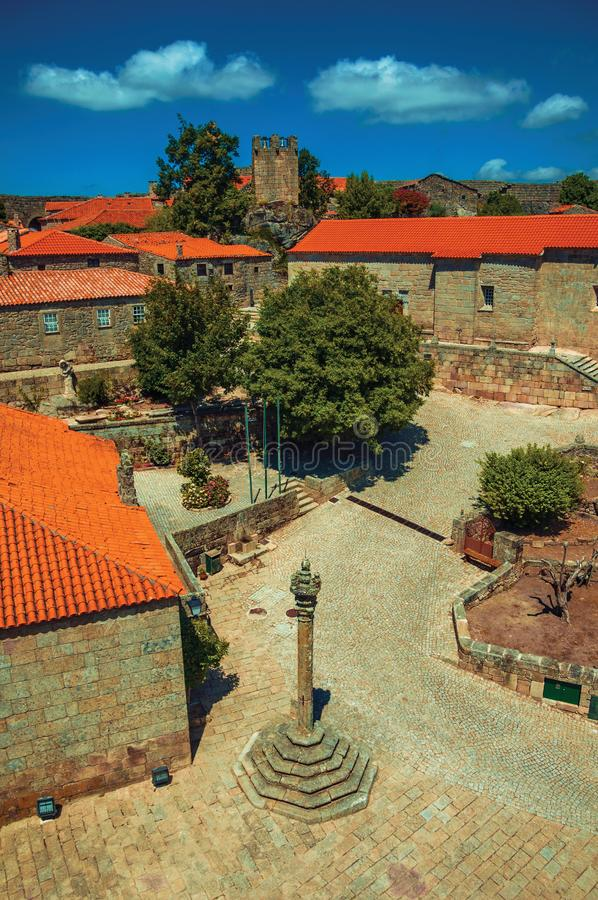 Stone houses and chapel encircling a square with pillory. Stone gothic houses and deserted square on slope with pillory, in a sunny day at Sortelha. One of the stock photography