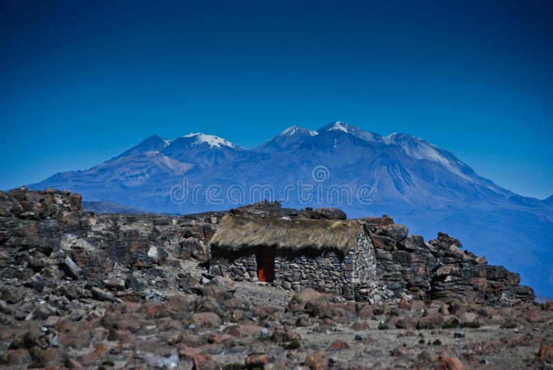 Stone hut and mountains in the background royalty free stock image
