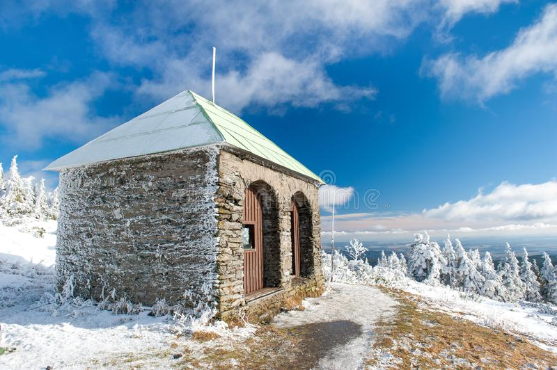 Stone hut / shelter Jeleni studanka in Jeseniky mountains in Czechia during nice winter day with clear sky. Wiew of Czech cottage. And trees covered in snow royalty free stock photos