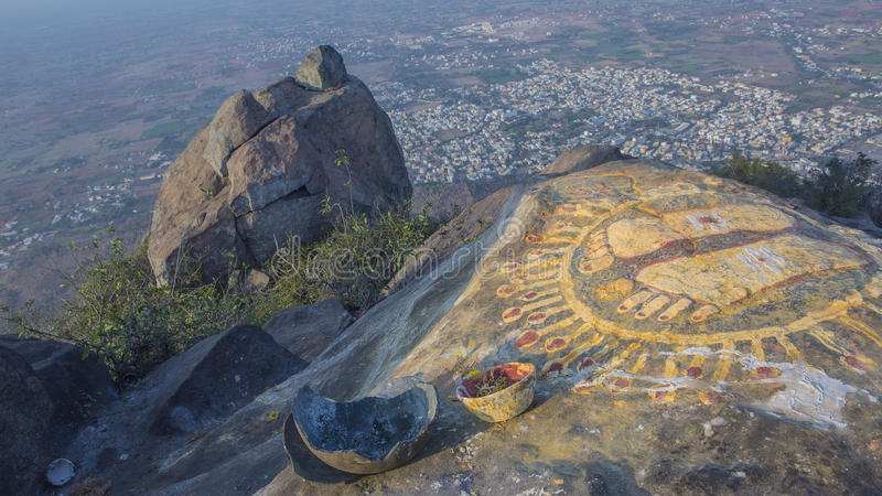 A stone with the image of the footprints of a guru on top of a m. Ountain Arunachala. Top view of the Tiruvannamalai city and Arunacheshvara Shiva Temple from royalty free stock images