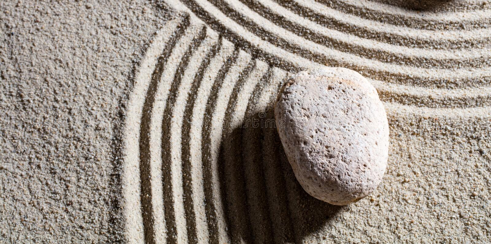 Stone at intersection of different roads for flexibility with serenity. Zen sand still-life - one stone at the intersection of different roads for concept of stock photography